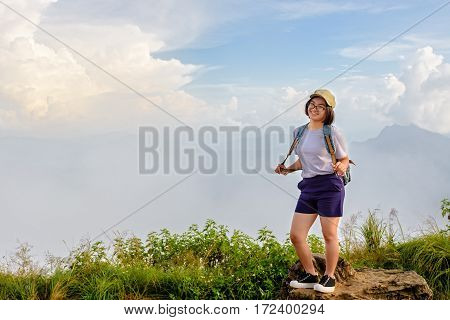 Tourist teens girl hiker with backpack cap and glasses is standing smile and poses happily at high mountain on sky and fog background at scenic point of Phu Chi Fa Forest Park in Chiang Rai Thailand