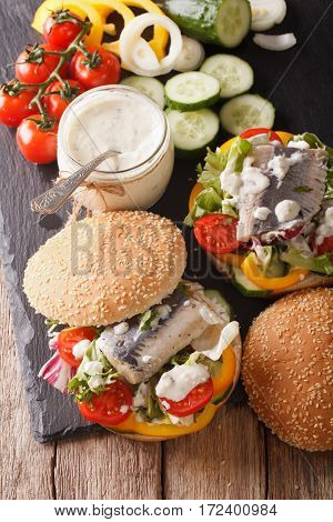 Fishburger With Herring, Gravy And Fresh Vegetables Close-up. Vertical