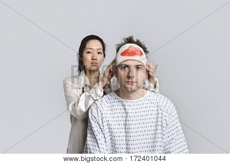 Portrait of female doctor examining injured male patient