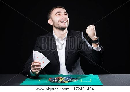 Man with four aces in hands playing on table in casino on black background