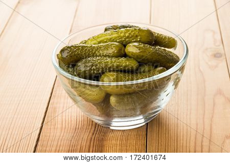 Heap Of Pickled Gherkins In Transparent Bowl On Table