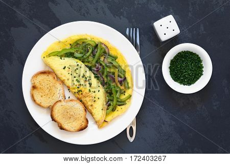 Omelette with green bell pepper and red onion sprinkled with chives served on plate with toasted and buttered bread slices photographed overhead on slate with natural light
