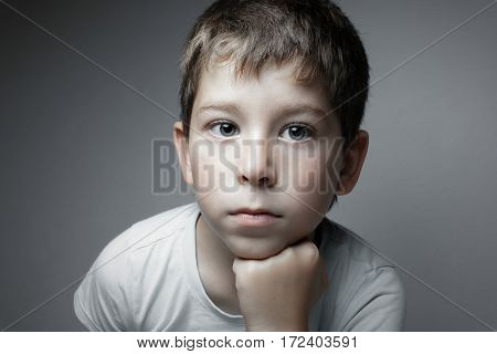 Portrait of a handsome boy looking in cam. Isolated on the gray background