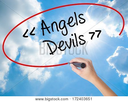 Woman Hand Writing Angels - Devils With Black Marker On Visual Screen.