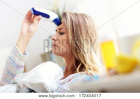 Picture showing sick woman with thermometer at home