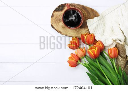 Overhead shot a bouquet of tulips with a cup of black steaming hot coffee and a cozy knit throw blanket over white wood table top. Flat lay top view style.