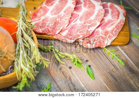 Raw beef, pork steak with herbs and spices on a rustic wooden table. Meat piece, copy space. Selective focus