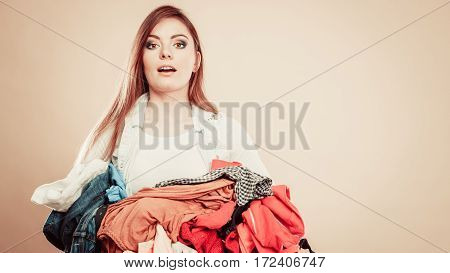 Daily routine in household laundry wash and ironing. Young girl hold pile of colorful clothes.