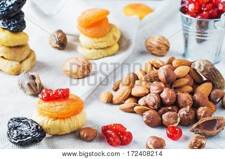 Mix of dried fruits and nuts almonds hazelnuts dried cherries dried apricots figs and prunes on on linen napkin. Healthy and wholesome food. The concept of natural organic food diet.