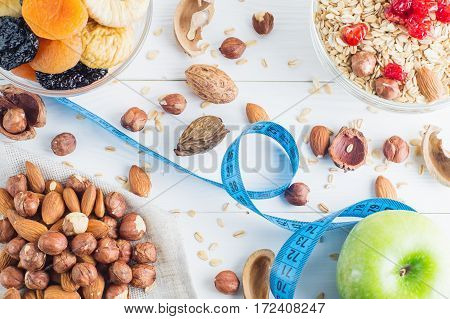 Healthy food. Ingredients for healthy breakfast on white wooden background. Oatmeal dried cherry and nuts measuring tape and apple top view. The concept of natural organic food diet.
