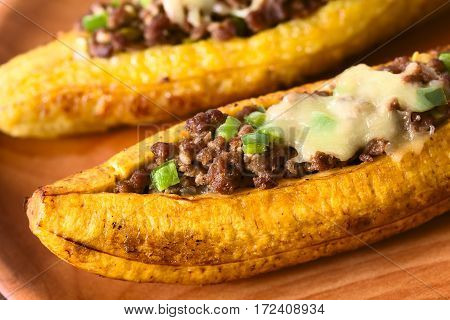 Baked ripe plantain stuffed with mincemeat olive green bell pepper and onion sprinkled with cheese a traditional dish in Central America called Canoa de Platano (Plantain Canoe) photographed with natural light (Selective Focus Focus in the middle of the i