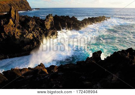 Waves breaking at the cliffs in front of the Ana Kai Tangata Cave close to Hanga Roa in Rapa Nui Easter Island in Chile South America
