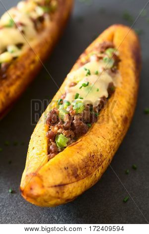 Baked ripe plantain stuffed with mincemeat olive green bell pepper and onion cheese on top sprinkled with chives a traditional dish in Central America called Canoa de Platano (Plantain Canoe) photographed on slate with natural light (Selective Focus Focus poster