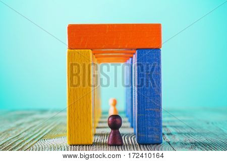 Abstract man into the colorful wooden corridor with copy space. Concept of success. Abstract man in a multicolored wooden tunnel. Two persons walk to the light in the end of the tunnel.