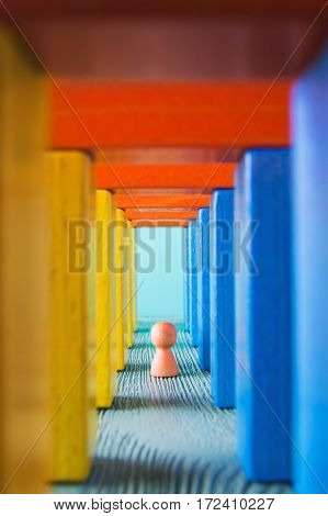 Abstract man into the colorful wooden corridor. Concept of success. Abstract man in a multicolored wooden tunnel.