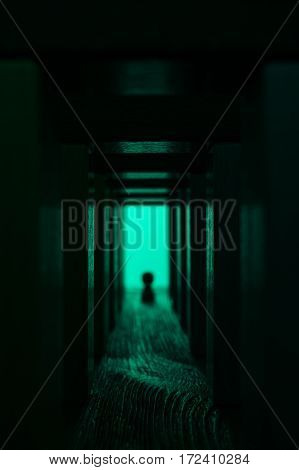 Light at the end of tunnel. A silhouette near the exit from abstract hallway. Abstract man walking in mystic wooden corridor with bright light.