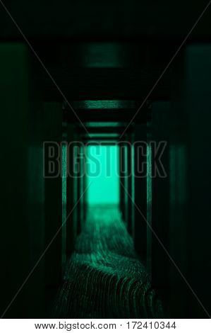 Light at the end of tunnel. Exit from abstract hallway. Mystic wooden corridor with bright green light.