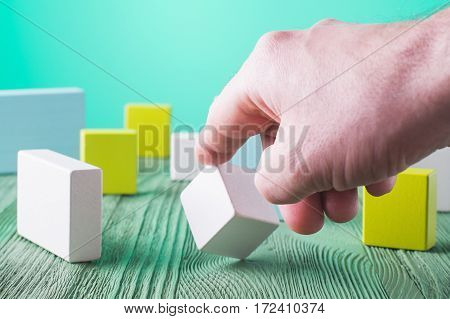 Hand holding wooden cube element. The concept of logical thinking. Geometric shapes on a wooden background. Man's hand holding wooden block. Colorful wooden blocks.