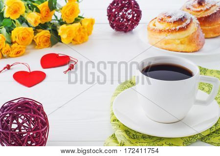 Cup of coffee with bouquet of yellow roses with copy space close-up. Two spiral tasty buns with coconut chips cup of black coffee and bouquet of roses. Delicious breakfast sweet rolls and coffee.
