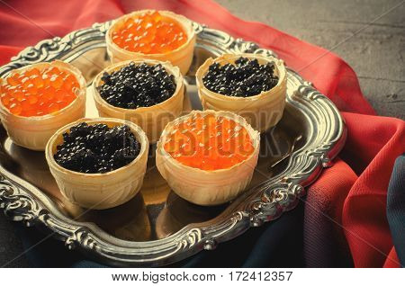 Black and red caviar tartlets, appetizer canapes on silver tray, horizontal, toned