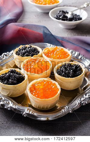 Black and red caviar tartlets, appetizer canapes on silver tray, vertical