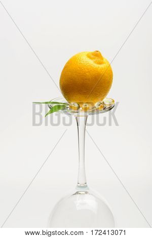 lemon with sheet and capsule on wineglass isolated on white background side view