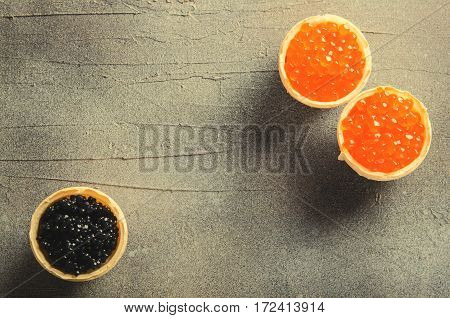 Black and red caviar tartlets, appetizer canapes on gray background, horizontal, copy space, top view, toned