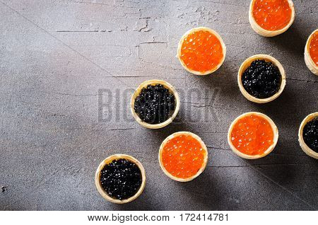 Black and red caviar tartlets, appetizer canapes on gray background, horizontal, copy space, top view