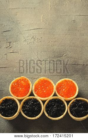 Black and red caviar tartlets, appetizer canapes on gray background, vertical, copy space, top view