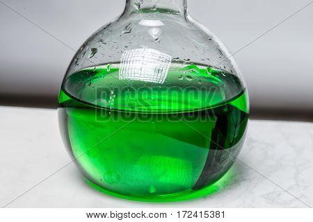 Green liquid in glass flask in laboratory