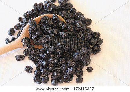 Dried blueberries on a wooden spoon ready to eat