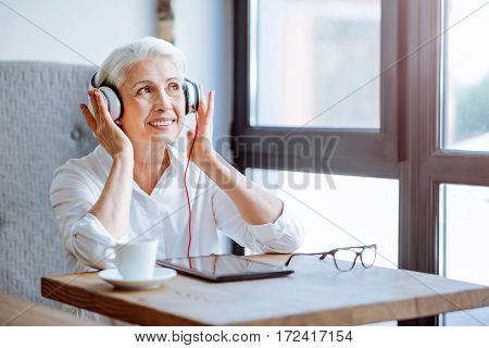 Enjoy nice sounding. Cheerful aged woman wearing headphones and listening to music while resting in the cafe