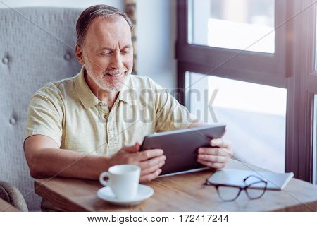 Have a nice day. Cheerful content aged man sitting at the table and using laptop while spending time in the cafe