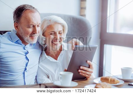 Stay modern. Positive delighted loving couple sitting in the cafe and using tablet while expressing gladness