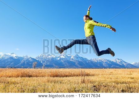 Happy Young Woman Jumping On A Mountain Meadow.
