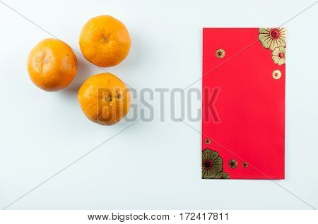Red packet and mandarin oranges on white background. Isolated