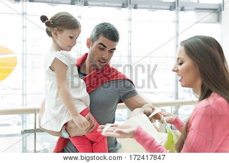 Father and daughter look into mothers shopping bag