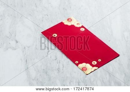Chinese new year. Red packet on white marble background. Isolated