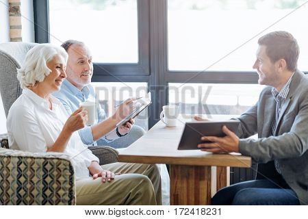 Ensure your future. Positive delighted loving aged couple sitting at the table and having a meeting with life insurance agent while talking with him