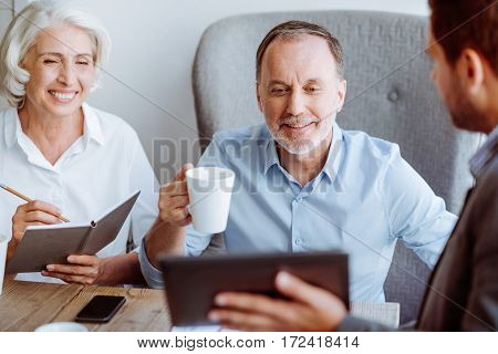 Different options. Pleasant smiling aged couple sitting in the cafe and meeting with sales manager while being involved in discussion