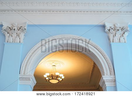 white arch on a blue wall inside the building and two pilasters