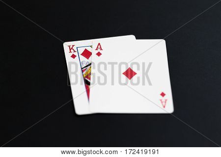 Playing poker cards ace king on black background.