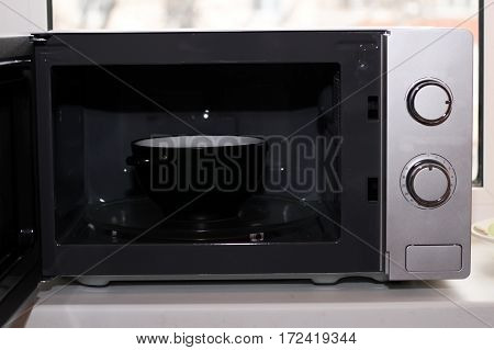 Microwave kitchen appliances a quick hot lunch. Grey color