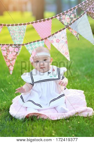little girl in white dress sitting on the grass in the park.