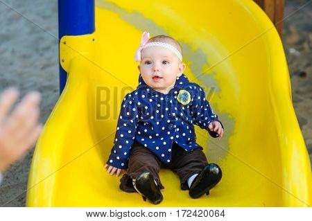 little baby girl slides down on the yellow game hill on a spring day