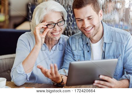 Full of joy. Cheerful content smiling woman aged woman and her grandson using tablet