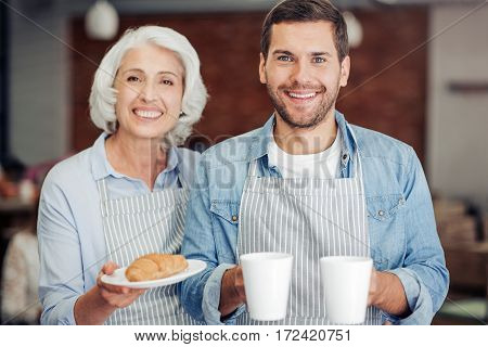 Family business. Positive delighted woman and her grandson owning the cafe nad welcoming guests while expessing gladness