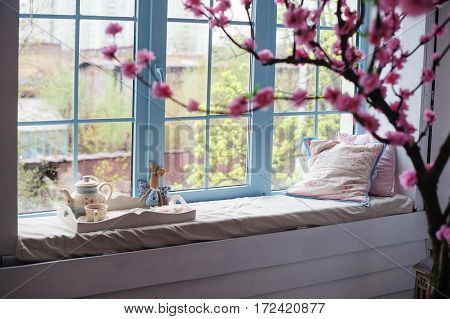 salver with tea and pillows on the window sill and a branch of apple blossoms in the foreground