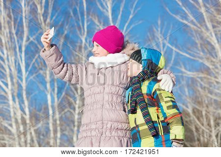 Two happy kids making selfie photo in winter park