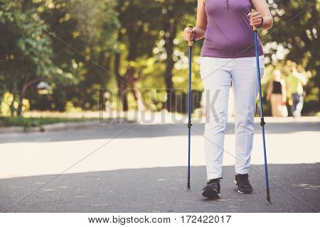 Nordic walking. Close up of walking poles being in use by a nice elderly sporty woman while practicing Nordic walking